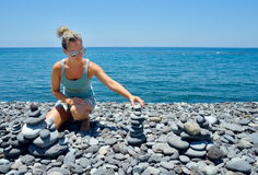 Young woman building stone stacks on pebble beach Royalty Free Stock Photography