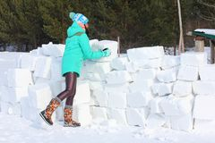 Young woman builds snow castle wall of snow blocks. Winter vacation. Winter and new year holidays. Young woman builds snow castle wall of snow blocks. Winter stock photo