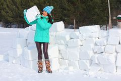 Young woman builds snow castle wall of snow blocks. Winter vacation. Winter and new year holidays. Young woman builds snow castle wall of snow blocks. Winter royalty free stock images