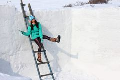 Young woman builds snow castle wall of snow blocks. Winter vacation. Winter and new year holidays. Young woman builds snow castle wall of snow blocks. Winter royalty free stock photography