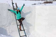 Young woman builds snow castle wall of snow blocks. Winter vacation. Winter and new year holidays. Young woman builds snow castle wall of snow blocks. Winter royalty free stock photo