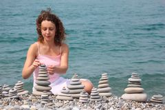 Young woman builds stone stacks on pebble beach Stock Images