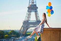 Young woman with bunch of balloons near the Eiffel tower Royalty Free Stock Photography