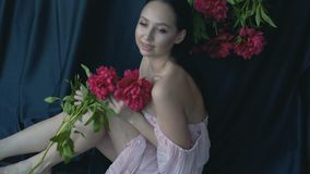 A young woman with a bunch of peonies posing for a camera in the studio. Slow motion stock video footage