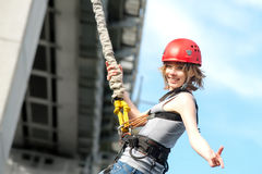 Young woman after the bungee jump. Beautiful young woman in a helmet hanging on a rope after the bungee jump against the sky Stock Photos