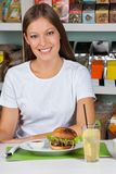 Young Woman With Burger And Drink At Table Stock Photos