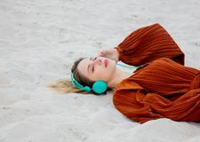 Young woman in burgundy color blouse with headphones lying down royalty free stock photos