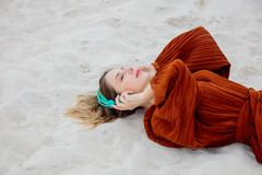 Young woman in burgundy color blouse with headphones lying down. On sand royalty free stock image