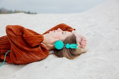 Young woman in burgundy color blouse with headphones lying down. On sand royalty free stock photography
