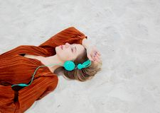 Young woman in burgundy color blouse with headphones lying down. On sand stock photos