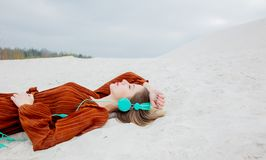Young woman in burgundy color blouse with headphones lying down. On sand royalty free stock photos