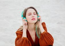 Young woman in burgundy color blouse with headphones royalty free stock photos