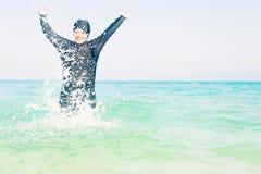 Young Woman In Burkini Splashing Water Stock Photos