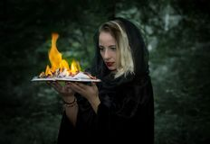 Young woman with a burning book in the forest. Stock Photo
