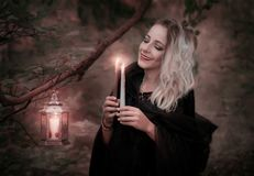 Young woman with burning candles in the forest. Halloween background Stock Photo