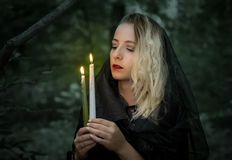 Young woman with burning candles in the forest. Royalty Free Stock Photo