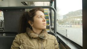 Young woman on the bus looking out the window. On the big city stock footage