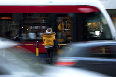 Young woman at a bus stop. Young woman waiting for a tram on city street, cars and trams passing by in motion blur Stock Image