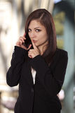Young woman in a business attire asks everyone to be quiet by pl Royalty Free Stock Image