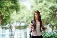 Young woman in business attire, carrying briefcase and holding f Stock Photos