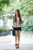 Young woman in business attire, carrying briefcase and holding f Royalty Free Stock Photos