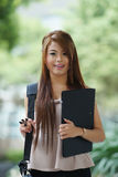 Young woman in business attire, carrying briefcase and holding f Stock Image