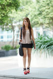 Young woman in business attire, carrying briefcase and holding f Royalty Free Stock Photography