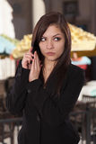 Young woman in a business attire places her hand over her phone Royalty Free Stock Photos