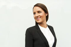 Young woman in business outfit looking left, in the city. Royalty Free Stock Photo