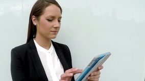 Young woman in business outfit over the glass wall using tablet. stock footage