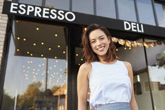 Young woman business owner standing outside cafe shopfront Stock Image