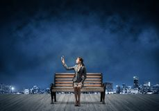 Young woman in business suit holding smartphone. With raised hand. Beautiful girl with mobile phone on wooden bench. Mobile marketing and digital technology stock images