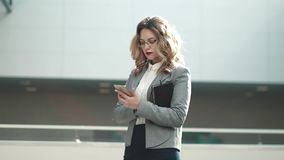 Young woman in business suit looks at notepad and typing message on mobile phone. portrait of a business woman in an. Business woman walking on business center stock video