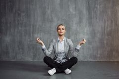 Young woman in business suit sitting in Lotus pose, restore energy, meditate. Health and work royalty free stock photos