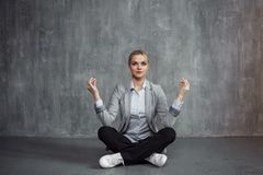 Young woman in business suit sitting in Lotus pose, restore energy, meditate. Health and work. Young woman in business suit sitting in the Lotus pose, restore Royalty Free Stock Photos
