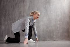 Young woman in business suit and sneakers. At a low start, ready to run a long distance stock images