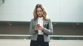 Young woman in business suit typing message on mobile phone. portrait of a business woman in an office building. Business woman walking on business center with stock footage