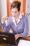 Young woman in business suit working from home Royalty Free Stock Photography