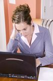 Young woman in business suit working from home Royalty Free Stock Images