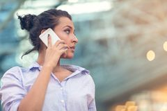 Young woman busy with calling, chatting on the cell phone side view portrait. royalty free stock photos