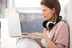 Young woman busy using laptop. Computer, concentrating on screen, having headphones in neck stock photography