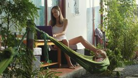 Young woman using laptop and swaying by foot hammock with her little daughter