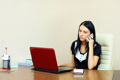 Young woman busy with work in office Royalty Free Stock Photo