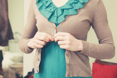 Young woman buttoning her blouse Royalty Free Stock Photography