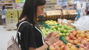 Young woman buying apples in the supermarket. stock video