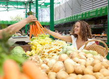 Young Woman Buying Carrots at Grocery Market. Young Smiling Woman Buying Carrots at Grocery Market Royalty Free Stock Images