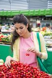 Young woman buying cherries Royalty Free Stock Photo