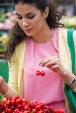 Young woman buying cherries Stock Image