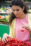 Young woman buying cherries Royalty Free Stock Photos