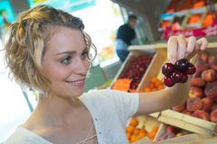 Young woman buying cherries weekly market Royalty Free Stock Photos